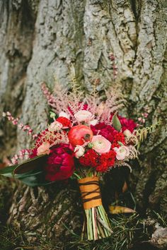 Shades of raspberry pink, coral, and blush; bouquet of ranunculus, peonies, coxcomb, and heather and red-tipped ti leaves -- a striking combination!