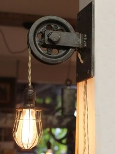 I think I may like the look of this one better. Must have. - Wall mount pulley light with caged Edison bulb.