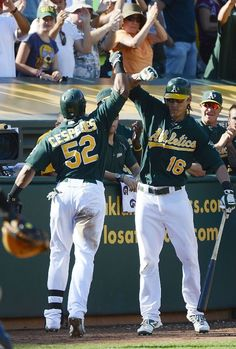 Yoenis Cespedes #52 of the Oakland Athletics is congratulated by Josh Reddick #16 after Cespedes hit a solo home run in the eighth inning against the Seattle Mariners at O.co Coliseum on September 30, 2012