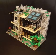 """betweenbrickwalls embedded a contemporary house in a rock wall. The """"green"""" house is highly sustainable, aided by solar panels and plenty of natural light for warmth. For good measure t… Lego Friends, Casa Lego, Construction Lego, Lego Pictures, Amazing Lego Creations, Lego Modular, House On The Rock, Lego Worlds, Lego Design"""