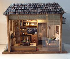 It is an artist made one of a kind Japanese restaurant. It is in a wooden box textured decoration paper exterior with dry banana leaf roof. It is about 11 wide 9  high 4 1/2 deep, closed with a light weight plexiglass front can be opened from the side. Small garden scene on the sides. LED light can be turned on and off . Hand made furniture ,sliding doors, dinner ware ,cabinet ........ It can be placed on table . Please contact me if you have any question