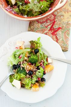 An expat's salad +stories from Japan. Lettuce, broccoli, apple, blueberries, pomegranate, walnuts, cheese, orange, red onion, shredded chicken