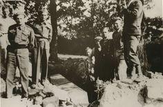 Nedtakingen av Nazistøtta og anlegget på Stiklestad er under arbeid i mai 1945. Her er bautaen nedtatt, brukket og klar for nedgraving. Verdalinger og norske soldater i engelsk uniform