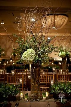 Tall designs of curly willow with antiqued hydrangea and lush foliages.