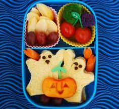 Lunch Box Halloween Meal - One Cupcake Mould filled with pealed Apple and Grape fingers - One Cupcake Mould filled with Broccoli and Cherry Tomatoes - Ghost Sandwiches - Carrot Sticks - Pumpkin Persimmon