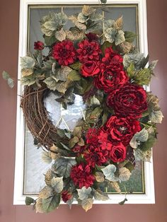 This beautiful wreath features an elegant display of gorgeous deep red peonies, roses, hydrangeas and dahlias. The focal point is another big beautiful deep red peony centered among very realistic variegated swirling cottonwood greenery all cascading down one side. I just love this