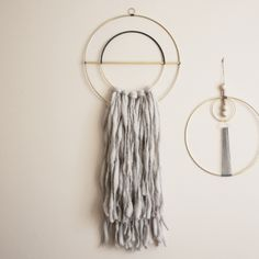 """Attalie Dexter  This wall hanging is composed of segmented brass rings wrapped in hand dyed  waxed linen with vintage brass details.  Hand spun wool fringe. Available in light grey (pictured) or off-white.  Total dimensions are 12"""" wide and 30"""" tall. The longer fringe extends 17.5"""" from the bottom."""