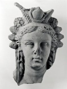 2ndC BC(early) Greece. Head from terracotta bust (?) of Isis, wearing head-dress consisting of a pair of horns supporting a disk and flanked by ears of corn, the crown of the head-dress forms a space that could have been used as an incense burner (though no traces of burning), below the crown wearing a wreath to which rosettes and leaves are attached, hair centrally parted and drawn back in waves, wearing long pendant earrings.  Light brown clay with a grey core (very little mica and a few…