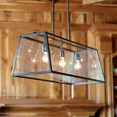 ballard's eldridge rectangular chandelier -simple geometric design with clear glass shade - architectural statement - tempered glass is framed by powder-coated steel with an antique bronze finish- hang this industrial chandelier over a kitchen island or long dining table