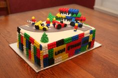 Race Car Lego Cake: top has a partial racetrack w/fondant cars and men; built up lego wall (looks so good not sure if they're real lego bricks or edible) with B-day inscription, sides of rectangular cake are (edible) tops. From CakeCentral.com
