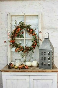 fall scene with old window dressed up with a fall wreath and a metal lantern