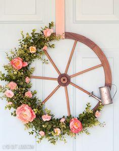 Farmhouse Wagon Wheel Spring Wreath #springwreath #farmhousewreath #farmhousedecor  via @LydiOutLoud