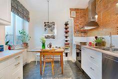 Cocina blanca con comedor de diario y pared de ladrillo visto