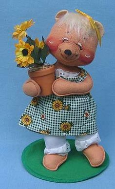 This doll features a Tan body, blonde hair with yellow bow, green plaid sunflower print dress, white eyelet lace pantaloons, holds clay flower pot with sunflowers, green felt base. Companion is 094396 - Country Boy Bear with Wheelbarrow. If you would like to purchase this doll please visit http://www.suecoffee.com/Annalee-10-INCH-Country-Girl-Bear-with-Flower-Pot-Mint-094296.html