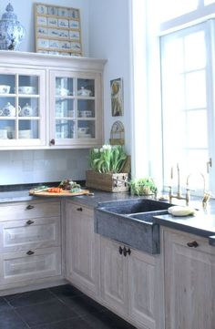 Klassieke keuken in massief eiken, afwerking gepatineerd. Belgisch hardstenen aanrechtbladen en dubbele spoelbak, randafwerking gefrijnd. Bovenkasten met glazen deuren met roedeverdeling - The Living Kitchen by Paul van de Kooi