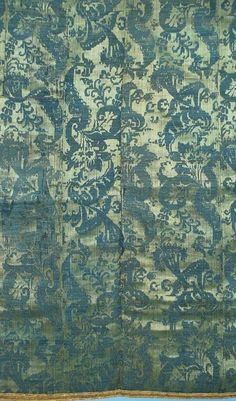 """18th Century Continental Silk Linen Lampas Fragment In Indigo And Emerald """"Saturated indigo blue with an emerald supplementary weft. In a vertical stylized botanical design. The total panel made up of 4 narrow panels, backed in linen that does not look period, perhaps 19th century. Bound on 4 sides in what looks like old gold trim. In fair antique condition with some abraded areas some early mends, these areas make more visible the hand spun linen threads."""""""