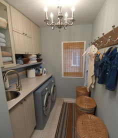 Perfect for a small laundry space! Love the chandelier, the hooks (make-shift mudroom/laundry), and the laundry baskets (one for each family member)