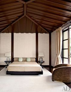 A guest room is appointed with an Armani/Casa bed, side tables, and barrel-back chair.