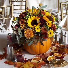 Fall wedding centerpiece made of silk flowers in faux pumpkin