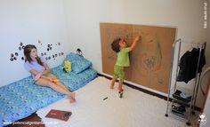 quarto montessoriano para criança de 2 anos: colchão no chão, tapete, um grande papel pardo na altura da criança para ela poder desenhar verticalmente, uma fruteira antiga que virou uma arara de roupas com lugar para sapatos.