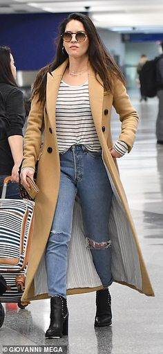 d13563e4306fa Olivia Munn wears camel coat over striped top and ripped jeans at LAX