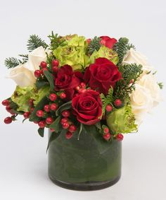 Splendid Roses - A wonderful collection of all red, green and white roses accented with red berries and seasonal greens.