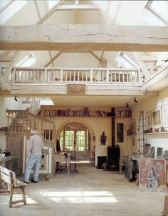 Old barn converted into an artist's studio in Normandy, France. High ceilings, wood stove, arched doorway, mounted bookshelves, windows, loft.