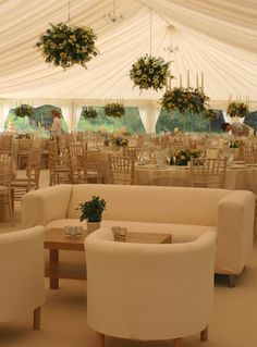 Stylish wedding marquee with hanging flower baskets, dining tables and sofas