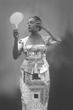 Carrie Mae Weems -self portrait in a quilted log cabin pattern dress.