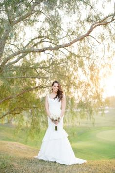 David's Bridal bride Griselda in a sophisticated mermaid style wedding gown with tiered skirt and bow detail in the back.