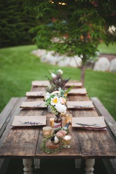 summer party. Old beer bottle vases, brown paper over plates. Simple and lovely.