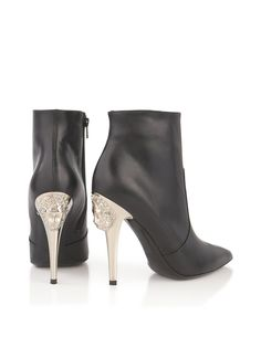 VERSUS VERSACE High Heel Ankle Boot - Black A little bit rock and roll, Versus Versace's Lion Head Ankle Boots feature a sharp pointed toe and vertiginous heel to add edge to your everyday looks. The contrasting silver heel gleams with a mirror-like finish and features the label's iconic lion head, adding decorative detail to an otherwise minimalist design. Lion Head Ankle Boot by Versus VersaceHeel height: 12cm BlackPointed toeInterior zip closureSilver-toned heelLion head detail to…