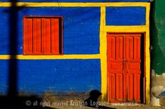 Blue wall of a house with red doors and yellow lines in Concepcion de Ataco El Salvador
