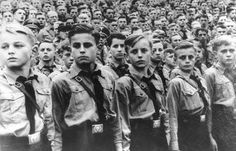 """Grim beyond their years, boys belonging to the Hitlerjugend (Hitler Youth) turn eyes at a Nazi rally. Their belt buckles carry the stern motto: """"Blood and Honor"""".  The Hitlerjugend admitted children at the age of 10, and continued until the age of 18. It was organized on a military pattern and prepared a young man to become a soldier or an SS. The young men were indoctrinated with the Nazi ideology."""