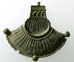 Pilgrim-badge; lead alloy; form of purse or scallop shell; lower part spreading out like fan; radiated pattern, beaded border and three tassels.