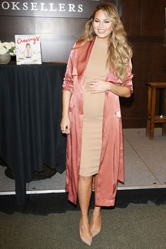 23 February Chrissy Teigen showed off her growing baby bump in a nude dress and a pink silky duster coat for a book signing in Los Angeles.   - HarpersBAZAAR.co.uk