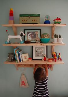 Nursery shelves of little treasures... cute mix of art, toys and books