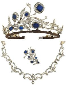 Tiara composed of central floral and foliate spray, each flower head w/cushion-shaped foil backed sapphire center to an old-cut diamond openwork surround, raised on similarly-set diamond stems and scrolling leaves. Graduated diamond Fleur-de-lys motif panels, partially closed set, mounted in silver and gold, the central spray with early 19th century elements detaching to form a brooch, the Fleur-de-lys panels forming a necklace, circa 1890, fitted S.J.Phillips Ltd. case. Image: Christie's.