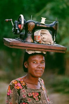 Mahafaly woman, a seamstress, carries her sewing machine, Southern Madagascar