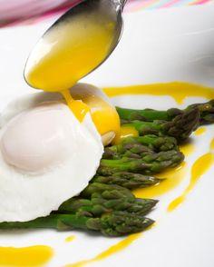 Huevo poché sobre una cama de espárragos acompañados de queso parmesano y  salsa holandesa y queso parmesano.