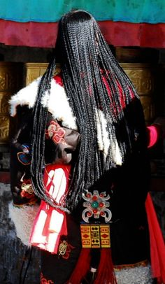 Tibetan woman at the temple in Lhasa.  Her hair is braided into the traditional 108 braids | via Quxizang website