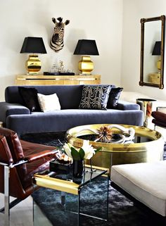 Living room with pair of brass lamps, zebra sculpture, and round coffee table