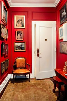 A scarlet red paint job excites the entryway, which is filled with one of Seligman's favorite collections, dog portraits.