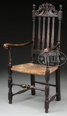 WILLIAM AND MARY BANNISTER BACK ARMCHAIR. Northern New England, Circa 1725. The back with foliate carved Prince of Wales cresting, four bannisters and shaped lower rail. Flanked by turned posts corresponding to turnings of bannisters, with urn and ball finials. The carved and molded arms have rams horn handholds, front legs with block and turned ring and urn elements and ball feet. The front stretcher of bold scale with central reel and bulbous turnings.