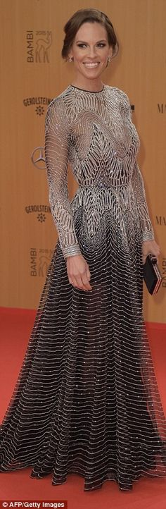 Million dollar look: Hilary Swank looked radiant in a dazzling silver dress featuring intr...