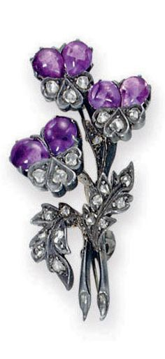 AN ANTIQUE AMETHYST AND DIAMOND BROOCH Designed as a cluster of cabochon amethyst pansy blossoms, with rose-cut diamond scrolling leaves, mounted in silver and gold, late nineteenth century, with French importation mark