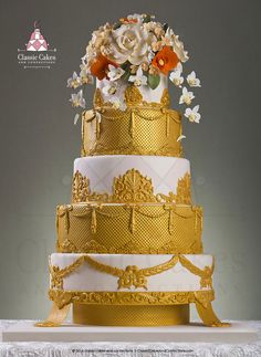 Ivory and gold wedding cake with ivory and orange sugar flowers.