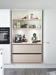 Cupboard doors fold into cupboard exposing bench with big appliances hidden away, but easy to access and use.