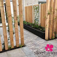 Een houten constructie voor een pergola dat tevens de klimplanten voorziet van klimsteunen. De zwarte balken zijn gebruikt om de border te verhogen. Zo komten de planten mooier uit tegen de schutting omdat het al wat hoger is.