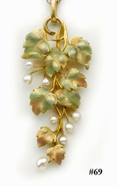 """Enamel, natural pearl and gold vine pendant and chain.English. """"This is a wonderful example of a piece of Art Nouveau jewelry combining beautiful pastel toned enamel with peg set natural pearls on intricate carved yellow gold leaves. Suspended from a finely linked yellow gold chain."""""""